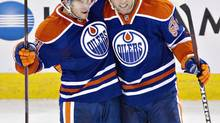Edmonton Oilers Taylor Fedun (81) and Ben Eager (55) celebrate a goal against the New York Rangers during second period NHL preseason action in Edmonton, Alta., on Tuesday September 24, 2013. (JASON FRANSON/THE CANADIAN PRESS)