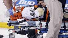 Pittsburgh Penguins' Brooks Orpik is taken off the ice after being injured in the first period of an NHL hockey game against the Boston Bruins in Boston, Saturday, Dec. 7, 2013. (MICHAEL DWYER/AP)