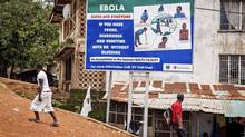 People walk past a billboard encouraging people suffering from symptoms linked to Ebola to present themselves at a health facility for treatment in Freetown, Sierra Leone, Thursday, Aug. 7, 2014. THE CANADIAN PRESS/AP-Michael Duff