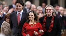 Liberal leader Justin Trudeau, left, and Member of Parliament Carolyn Bennett, right, escort recently elected Member of Parliament Chrystia Freeland in the House of Commons on Parliament Hill in Ottawa Jan. 27. (CHRIS WATTIE/REUTERS)