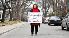 Paisley Rae holds a sign that appears in a PSA she developed in partnership with the Toronto police around the Parkdale attacks. (Jennifer Roberts for The Globe and Mail/Jennifer Roberts for The Globe and Mail)