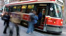 Passengers board a TTC streetcar; the TTC come under fire recently over rider photos and videos of what they deem unacceptable service. (Peter Power/Peter Power/THE GLOBE AND MAIL)