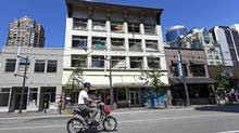 A man on a scooter drives past the Clifton Hotel on Granville Street in the heart of downtown Vancouver July 11, 2013. The city of Vancouver is applying to the Supreme Court to force the owners of this hotel to do a raft of repairs after eight months of inspections by city showed massive problems -- leaks, creative wiring, no water at times, possible structural problems. Council approved going to court for an injunction. This building currently at the top of the list of problem properties in the city. (Jeff Vinnick/The Globe and Mail)