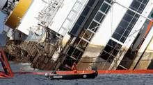 """Salvage crew workers are seen in front of the capsized Costa Concordia cruise liner after the start of the """"parbuckling"""" operation outside Giglio harbour September 16, 2013. Engineering teams began lifting the wrecked liner upright on Monday, the start of one of the most complex and costly maritime salvage operations ever attempted. The operation will see the ship rotated by a series of cranes and hydraulic machines, pulling the hulk from above and below and slowly twisting it upright. (TONY GENTILE/Reuters)"""