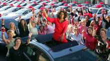 Talk show host Oprah Winfrey surrounded by some of the 276 people from her audience who each received one of the new cars at the start of the show to celebrate the premier of her 19th season. (Bob Davis)
