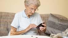 Sad older woman looks at empty wallet (Annett Vauteck/Photos.com)