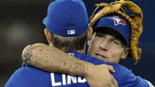 Toronto Blue Jays third baseman Brett Lawrie (back) and first baseman Adam Lind celebrate their win against the Seattle Mariners during the ninth inning of their MLB American League baseball game in Toronto April 28, 2012. REUTERS/Mike Cassese (MIKE CASSESE)