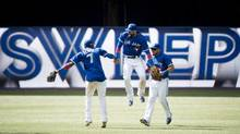 Toronto Blue Jays teammates Jose Reyes, Jose Bautista and Melky Cabrera celebrate after sweeping the Oakland Athletics (Nathan Denette/THE CANADIAN PRESS)