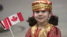 Three-year-old Zahar Murad waves flags as she watches the annual Canada Day parade in Montreal, Monday, July 1, 2013. (Graham Hughes/THE CANADIAN PRESS)