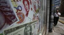 Photos of yuan (top) and U.S. dollar banknotes are displayed at a money exchange in Hong Kong Sept. 13, 2010. (BOBBY YIP/REUTERS/BOBBY YIP/REUTERS)