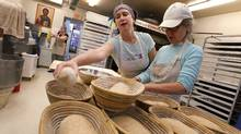 Staff member Christine Lefloch, left, making red fife sour dough, and showing volunteer Susan, right, how to roll the dough at St. John's Bakery in Toronto on Tuesday, October 19, 2010. (Peter Power/Peter Power/The Globe and Mail)