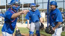 Toronto Blue Jays catchers J.P. Arencibia, left, Josh Thole, centre, and Henry Blanco chat before a drill during baseball spring training in Dunedin, Fla., on Thursday, Feb. 21, 2013. (Nathan Denette/THE CANADIAN PRESS)