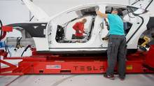 Workers add seat belts to a Telsa Motors Inc. sedan at the company's assembly plant in Fremont, Calif. in this July 10, 2013 file photo. In a sign of this enthusiasm, Robert W. Baird & Co. upgraded its Tesla rating on Monday following a factory tour. (Noah Berger/Bloomberg)