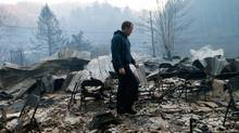 Trevor Cates, walks through the smoldering remains of the fellowship hall of his church, the Banner Missionary Baptist Church as he inspects damage after a widfire November 29, 2016 in Gatlinburg, Tennessee. Thousands of people have been evacuated from the area and over 100 houses and businesses were damaged or destroyed. Drought conditions and high winds helped the fire spread through the foothills of the Great Smoky Mountains. (Brian Blanco/Getty Images)