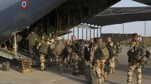 French troops board a transport plane in Ndjamena, Chad on Jan. 12, 2013. French forces carried out a second day of air strikes against Islamist rebels in Mali on Saturday and sent troops to protect the capital Bamako in an operation involving several hundred soldiers, Defence Minister Jean-Yves Le Drian said. (REUTERS)