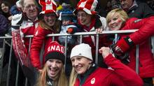 Canada's Heather Moyse and Kaillie Humphries hug their family members after winning gold February 19, 2014 in the women's bobsled competition at the Sochi Games. (John Lehmann/The Globe and Mail)