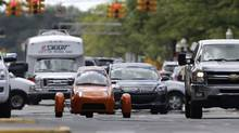 The Elio, a three-wheeled prototype vehicle, is shown in traffic in Royal Oak, Mich., Thursday, Aug. 14, 2014. (Paul Sancya/AP Photo)