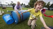 "Children play at the mobile ""Adventure Playground"" in Calgary, Alberta. Kids are encouraged to build things out of supplied material that include hammers, nails, saws, tires and tape without parents being involved. (Todd Korol/Todd Korol/Globe and Mail)"