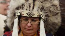 Attawapiskat Chief Theresa Spence, wearing a headdress, takes part in a drum ceremony before departing a Ottawa hotel to attend a ceremonial meeting at Rideau Hall with Gov. Gen. David Johnston in Ottawa, Friday January 11, 2013. (FRED CHARTRAND/THE CANADIAN PRESS)
