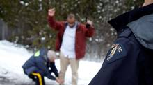 A man from Yemen is taken into custody by Royal Canadian Mounted Police (RCMP) officers after walking across the U.S.-Canada border into Hemmingford, Quebec, Canada February 14, 2017. (CHRISTINNE MUSCHI/REUTERS)