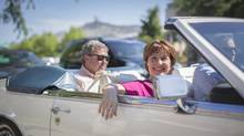 Ben Stewart (L) who stepped down for Premier Christie Clark (R) ride off convertible cadillac after visiting a coffee shop in Kelowna July 10, 2013 on election day. (John Lehmann/The Globe and Mail)