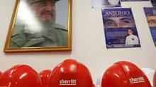 Security helmets displaying the logo of Sherritt International can be seen in front of a picture of Fidel Castro at Energas, a natural gas plant run as a joined venture between the Canadian company and the Cuban government. (Fernando Morales/The Globe and Mail)