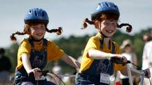 Identical twin sisters ride a tandem bicycle during a street parade at the 32nd annual Twins Days Festival in Twinsburg, Ohio. (JASON REED)