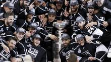Los Angeles Kings players pose with the Stanley Cup after they defeated the New Jersey Devils in Game 6 of the NHL Stanley Cup hockey final in Los Angeles, June 11, 2012. (Reuters)
