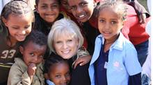 Imagine Adoption director Susan Hayhow is shown surrounded by children during a visit to Ethiopia.