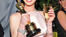 Anne Hathaway poses with her award for best actress in a supporting role for Les Misérables at the Governor's Ball following the Oscars at the Dolby Theatre on Sunday Feb. 24, 2013, in Los Angeles. (Vince Bucci/AP)