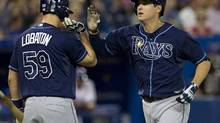 Tampa Bay Rays Kelly Johnson (right) is congratulated by teammate Jose Lobaton after hitting a homer off Toronto Blue Jays starting pitcher Ramon Ortiz during second nning AL action in Toronto on Tuesday May 21, 2013. THE (Frank Gunn/The Canadian Press)