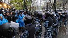 Riot police separate opposition and pro-government activists outside an election precinct in Kiev. (Sergei Chuzavkov/AP)