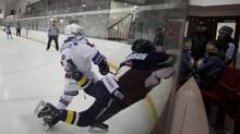 "In this file photo, Flamborough's Chris Addison, in blue, goes head first into the corner boards off a hit from Oakville's Himmat Dhillon. Dhillon received a penalty on the play. Addison was not injured. , The Oakville Rangers defeated the Flamborough Sabres 6-0 in Pee Wee ""AE"" action in Oakville on Feb. 2, 2011 (PETER POWER/THE GLOBE AND MAIL)"