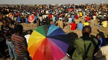Striking miners gather as they listen to the ministerial task team (not pictured) outside a South African mine in Rustenburg, 100 km (62 miles) northwest of Johannesburg Aug. 21, 2012. (SIPHIWE SIBEKO/REUTERS)