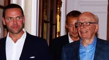 The chief executive of News Corp. in Europe and Asia, James Murdoch (L), escorts his father Rupert Murdoch (R), chairman of News Corp., on July 10, 2011 at his residence in London shortly after his arrival in Britain. (MAX NASH/Getty Images)