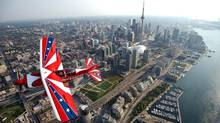 Aerobatic pilot Mike Wiskus flies his Lucas Oil Pitt plane over the Toronto shoreline during the preview for the 63rd annual Canadian International Air Show, August 31, 2012. (Galit Rodan/THE GLOBE AND MAIL)