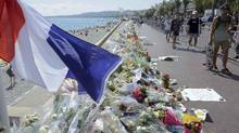 People walk past flowers left in tribute at a makeshift memorial to the victims of the Bastille Day truck attack near the Promenade des Anglais in Nice, France, July 21, 2016. (JEAN-PIERRE AMET/REUTERS)