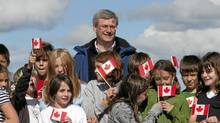 Prime Minister Stephen Harper among students from Ecole Emilie Tremblay, in Whitehorse, on Aug. 26. (Sean Kilpatrick/The Canadian Press)