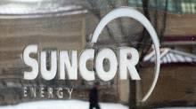 A pedestrian is reflected in a Suncor Energy sign in Calgary, in this file photo. (Jeff McIntosh/THE CANADIAN PRESS)