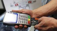 A customer uses a credit card at The Camera Store in Calgary, Alberta, on May 5, 2015. Albertans carried an average of $27,599 in consumer debt (excluding mortgages) in the third quarter of 2015, according to credit monitoring agency TransUnion – slightly less than one year earlier but still significantly higher than the national average of $21,247. (Todd Korol For The Globe and Mail)