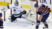 Edmonton Oilers' Ryan Nugent-Hopkins scores against Vancouver Canucks goalie Roberto Luongo during their NHL hockey game in Edmonton October 15, 2011. (DAN RIEDLHUBER/Reuters)