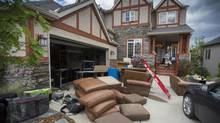 Gordon MacPherson, a home owner in Discovery Ridge, with his water soaked couch from his flooded basement June 22, 2013. (John Lehmann/The Globe and Mail)