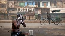 An Indian man bathes on a street as a rickshaw driver pedals past on a cold morning in New Delhi, Dec. 28, 2011. Economic growth in the world's most-populous nation is expected to drop below 6 per cent. (Kevin Frayer/Associated Press/Kevin Frayer/Associated Press)