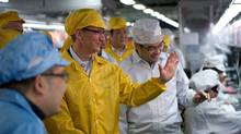Apple Chief Executive Officer Tim Cook talks to employees as he visits the iPhone production line at the newly built Foxconn Zhengzhou Technology Park, Henan province, in this March 28, 2012 file handout photo. Apple said March 29, 2012 it had agreed to work with partner Foxconn to substantially improve wages and working conditions at the factories that produce its products. (HANDOUT/REUTERS/Apple/Handout/Files)