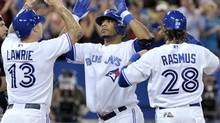 Toronto Blue Jays batter Edwin Encarnacion (C) celebrates with teammates Brett Lawrie (L) and Colby Rasmus after hitting his 40th home run of the year against the Seattle Mariners during the fourth inning of their American League baseball game in Toronto September 13, 2012. (MIKE CASSESE/REUTERS)