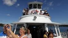 Tourists take pictures of the 1000 Islands during a tour of the St. Lawrence river near Gananoque Ont., Aug. 6, 2015. (Lars Hagberg For The Globe and Mail)