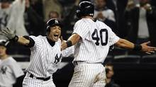 New York Yankees' Ichiro Suzuki, left, of Japan, celebrates with Francisco Cervelli (40) after Cervelli scored on an RBI single from Raul Ibanez during the 12th inning of a baseball game, Tuesday, Oct. 2, 2012, in New York. (Associated Press)