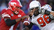 Calgary Stampeders quarterback Henry Burris (L) tries to get away from BC Lions Khalif Mitchell during the first half of their CFL football game in Calgary, Alberta, September 17, 2011. REUTERS/Todd Korol (TODD KOROL)