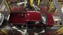 Robots do a quality control check of a 2014 Ford F-150 pick-up truck as it moves down the assembly line at the Ford Motor Dearborn Truck Plant in Dearborn, Michigan in this September 16, 2013 file photo. (REBECCA COOK/REUTERS)