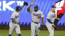 Los Angeles Dodgers Howie Kendrick, left, Yasiel Puig and Joc Pederson celebrate after the Dodgers defeated the Washington Nationals 4-3 in Game 1 of a baseball National League Division Series at Nationals Park, Friday, Oct. 7, 2016, in Washington. (Pablo Martinez Monsivais/AP)